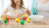Close up of little girl and mother coloring eggs — Stock Photo