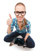 Smiling woman sitiing on floor with tablet pc — Stock Photo