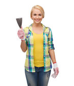 Smiling female worker in gloves with spatula — ストック写真