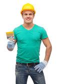 Smiling manual worker in helmet with paintbrush — Stok fotoğraf