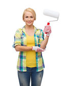 Smiling woman in gloves with paint roller — Stok fotoğraf