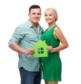 Smiling couple holding green paper house — Stock Photo