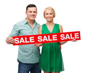 Smiling couple with sale sign — Stok fotoğraf