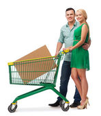 Smiling couple with shopping cart and big box — Stock Photo