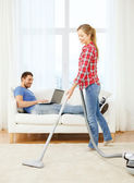 Smiling woman with hoover and man with laptop — Stock Photo