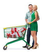 Smiling couple with shopping cart and gift boxes — Stock Photo