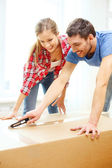 Smiling couple opening big cardboard box — Stock Photo