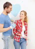 Smiling couple painting small heart on wall — Stock Photo