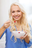 Smiling woman with bowl of muesli having breakfast — ストック写真