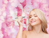 Beautiful woman with closed eyes and makeup brush — Stock Photo