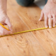 Close up of male hands measuring wood flooring — Stock Photo #42423199