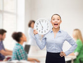 Attractive teacher with wall clock — Stock Photo