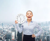 Attractive businesswoman with wall clock — Stock fotografie
