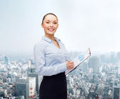 Young smiling businesswoman with clipboard and pen — Stok fotoğraf