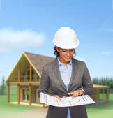 Businesswoman in white helmet with blueprint — Stock Photo