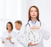 Calm female doctor with wall clock — Photo