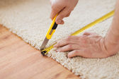 Close up of male hands cutting carpet — Stock Photo