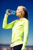 Mulher bebendo água depois de fazer esportes ao ar livre — Foto Stock