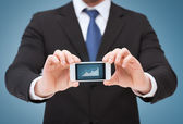 Man showing smartphone with graph on screen — Stock Photo