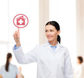 Smiling female doctor pointing to hospital sign — Stock Photo