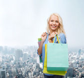 Smiling woman with many shopping bags — Stockfoto