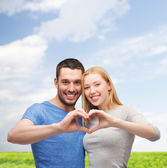 Smiling couple showing heart with hands — Foto Stock