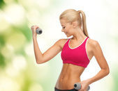 Young sporty woman with light dumbbells — ストック写真