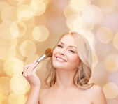 Beautiful woman with closed eyes and makeup brush — Foto Stock