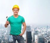 Smiling manual worker in helmet with hammer — Foto Stock