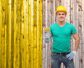 Smiling manual worker in helmet with paintbrush — Foto Stock
