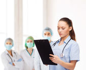 Serious female doctor or nurse with stethoscope — Stock Photo