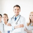 Male doctor in front of medical group — Stock Photo #42626485