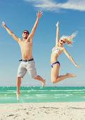 Paar am strand springen — Stockfoto