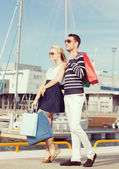 Young couple in duty free shopping bags — Stock Photo