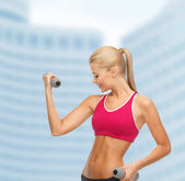 Young sporty woman with light dumbbells — Stockfoto
