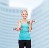 Junge sportliche frau mit leichten hanteln — Stockfoto