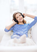 Smiling young girl in headphones at home — Foto Stock