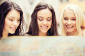 Beautiful girls looking into tourist map in city — Stock Photo