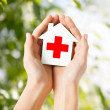 Hands holding paper house with red cross — Stock Photo #42813471
