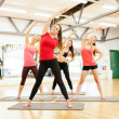 Group of smiling women stretching in the gym — Stockfoto