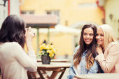 Beautiful girls taking picture in cafe in city — Stock Photo