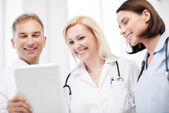 Doctors looking at tablet pc — Stock Photo