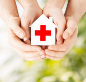 Hands holding paper house with red cross — Stock Photo