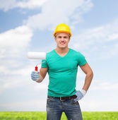 Smiling manual worker in helmet with paint roller — Stock Photo