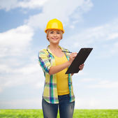 Smiling woman in helmet with clipboard — Foto Stock