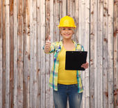 Smiling woman in helmet with clipboard — Stock Photo