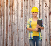 Smiling woman in helmet with clipboard — Stockfoto