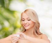 Beautiful woman applying cream — Stock Photo