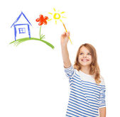 Cute little girl drawing house with brush — Stock Photo