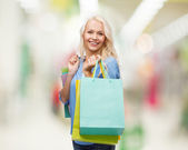 Smiling woman with many shopping bags — ストック写真